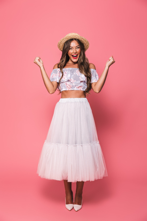 Full length portrait of beautiful excited woman 20s wearing straw hat and fluffy skirt laughing while clenching fists like winner isolated over pink background in studio