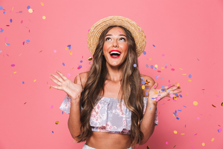Portrait of a cheerful young girl in summer clothes under confetti rain over pink background