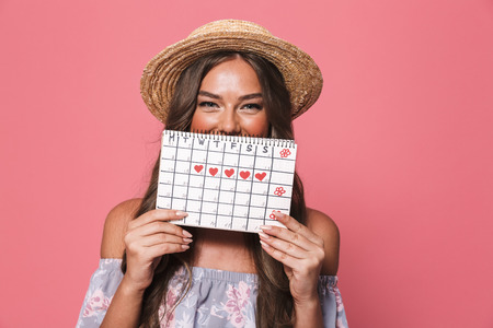 Portrait of beautiful european woman 20s wearing straw hat holding period calendar isolated over pink background in studio