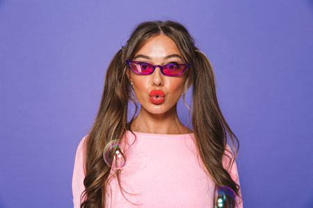 Portrait of a lovely girl in sweatshirt in sunglasses looking at camera isolated over violet background, soap bubbles on background Stock Photo