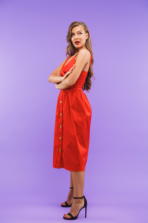 Full length portrait of elegant brunette woman 20s wearing red dress smiling and looking aside standing isolated over violet background
