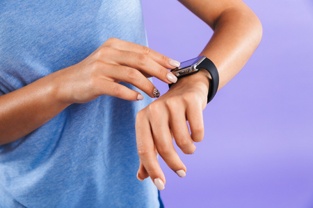 Close up of a young woman touching her smartwatch isolated over violet background Archivio Fotografico
