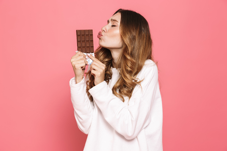 Portrait of a happy young woman kissing chocolate bar isolated over pink background