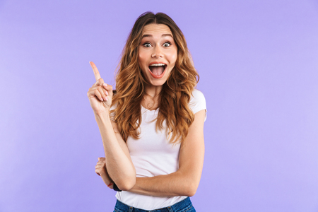 Portrait of a cheerful young girl standing isolated over violet background, pointing finger up Stock Photo