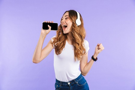 Portrait of a cheerful young girl holding mobile phone isolated over violet background, listening to music with headphones, singing