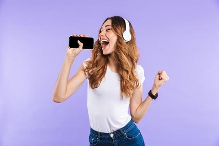 Retrato de una joven alegre sosteniendo teléfono móvil aislado sobre fondo violeta, escuchando música con auriculares, cantando