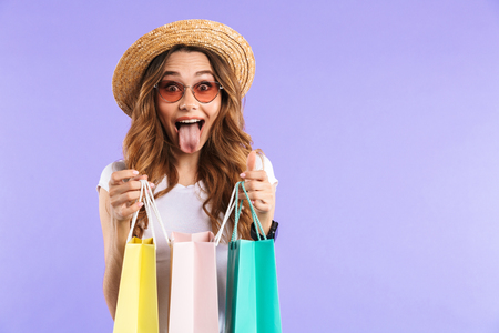 Photo of excited surprised cute woman isolated over purple wall background holding shopping bags showing tongue.