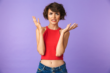 Portrait of a frustrated young girl shrugging shoulders isolated violet background