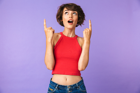 Portrait of a cheerful young girl pointing fingers up at copy space isolated violet background Stok Fotoğraf