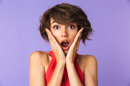 Portrait of a shocked young girl looking at camera with open mouth isolated violet background Stockfoto