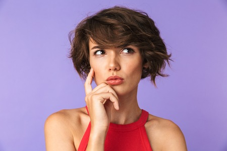 Close up portrait of a confused young girl thinking isolated violet background, looking away Stockfoto