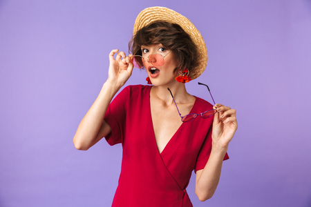 Portrait of a pretty young girl in straw hat holding two pairs of sunglasses isolated violet background