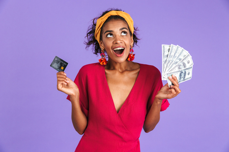 Cheerful african woman in dress holding money and credit card while looking up over purple background