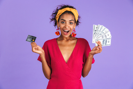 Surprised cheerful african woman in dress holding money and credit card while looking at the camera over purple background