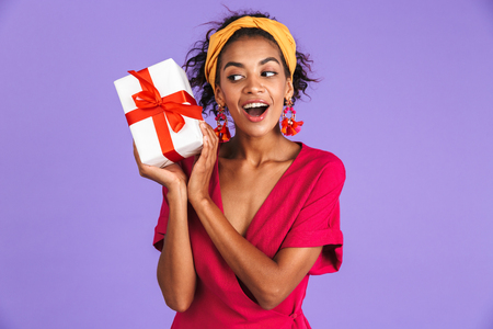 Picture of Happy intrigued african woman in dress holding gift box over purple background