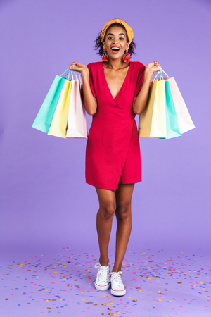 Full length portrait of a cheerful young african woman in headband standing over violet background, carrying shopping bags 版權商用圖片