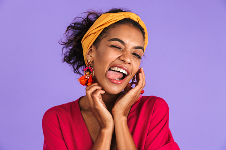 Portrait of a smiling young african woman in headband standing over violet background, sticking tongue out