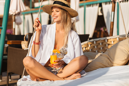 Photo of gorgeous woman 20s in straw hat smiling and holding orange juice while sitting on luxury sofa on beach during summer sunny day