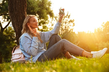 Portrait of a lovely young girl with backpack sitting on a grass at the park, taking selfie