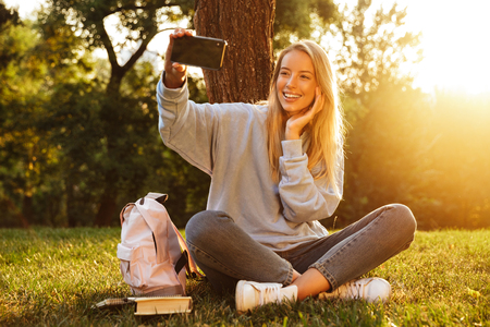 Portrait of a smiling young girl with backpack sitting on a grass at the park, taking selfie