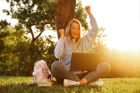 Portrait of a joyful young girl with backpack sitting with legs crossed, using laptop computer, celebrating Stock Photo