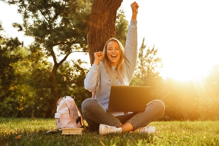 Portrait of a cheerful young girl with backpack sitting with legs crossed, using laptop computer, celebrating Stock Photo