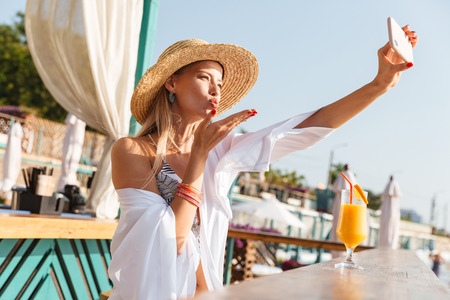 Photo of stunning blond woman 20s in straw hat smiling and taking selfie on mobile phone while drinking orange juice in beach bar during summer sunny day