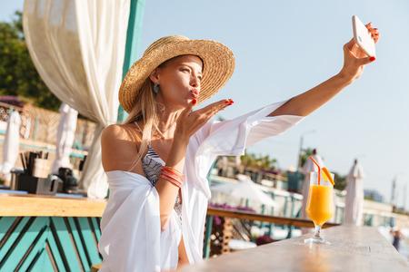 Foto de impresionante mujer rubia de 20 años con sombrero de paja sonriendo y tomando selfie en teléfono móvil mientras bebe jugo de naranja en el bar de la playa durante el día soleado de verano