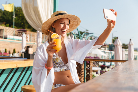 Photo of beautiful blond woman 20s in straw hat and swimwear taking selfie on mobile phone while holding orange juice in beach bar during sunbathing Stock Photo
