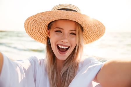 Photo of cheerful young woman 20s in summer straw hat laughing and taking selfie while walking on beach during sunrise Reklamní fotografie