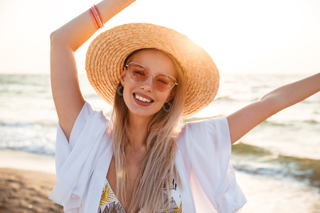 Image of beautiful blonde woman 20s in summer straw hat and sunglasses smiling while resting at seaside Reklamní fotografie