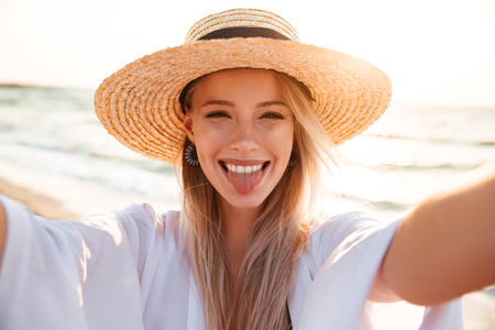 Photo of stylish happy woman 20s in summer straw hat laughing, and taking selfie while walking on beach Stock Photo