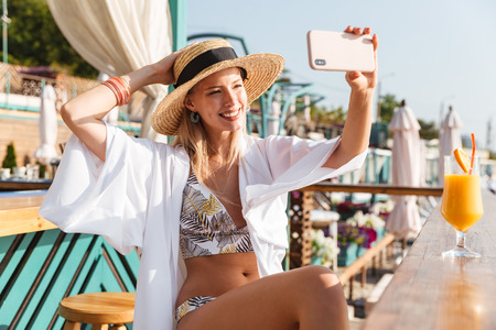 Photo of european pretty woman 20s in straw hat and swimsuit taking selfie on mobile phone while drinking orange juice in beach bar during summer sunny day