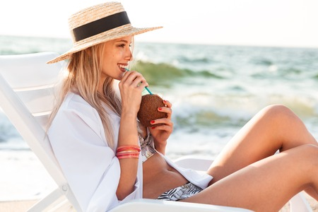 Smiling young girl in summer hat resting at the beach, drinking cocktail
