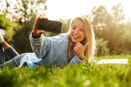 Portrait of a lovely young girl with book laying on a grass at the park, taking selfie, showing thumbs up