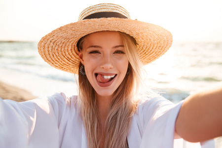 Photo of joyous blonde woman 20s in summer straw hat smiling and taking selfie while walking at sea coast in morning