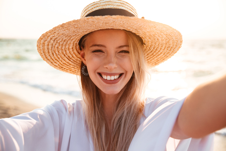 Portrait of caucasian pretty woman 20s in summer straw hat smiling and taking selfie while walking at seaside