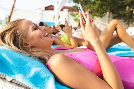 Smiling young woman dressed in swimsuit holding mobile phone while relaxing at the spa center resort