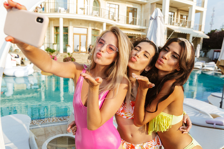 Three lovely young women in swimwear taking a selfie while having fun together at the swimming pool outdoors