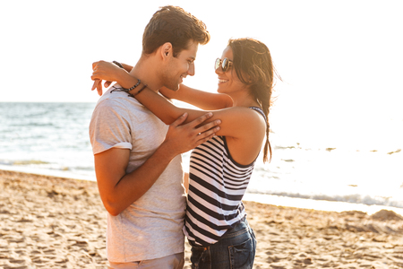 Picture of young cute loving couple hugging on the beach outdoors. Stock Photo - 108271131