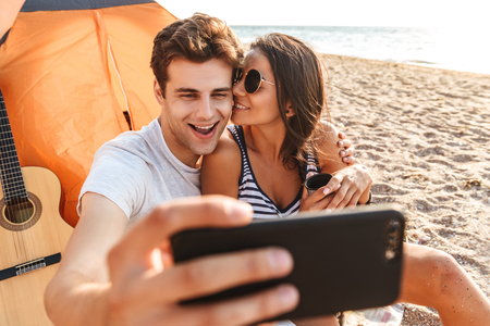 Cheerful young cute loving couple make selfie by mobile phone on the beach outdoors.