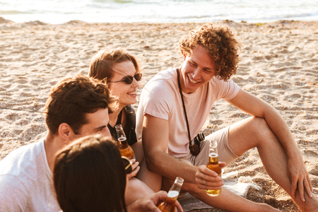 Photo of happy group of friends outdoors on the beach sitting while drinking beer.