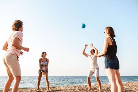 Photo of happy friends outdoors on the beach play volleyball having fun.