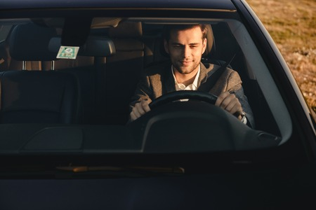 Front view of smiling bussinesman in suit driving his car Stock Photo