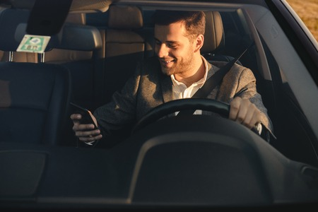 Front view of smiling bussinesman in suit driving his car, using mobile phone