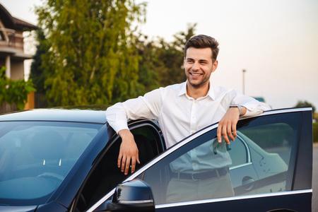 Portrait of handsome businesslike man wearing suit standing near his luxury black car with open driver's door