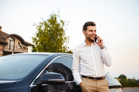 Portrait of handsome businessman wearing suit standing near his luxury black car and talking on mobile phone Stock Photo