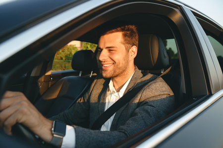 Confient smiling bussinesman in suit driving his car