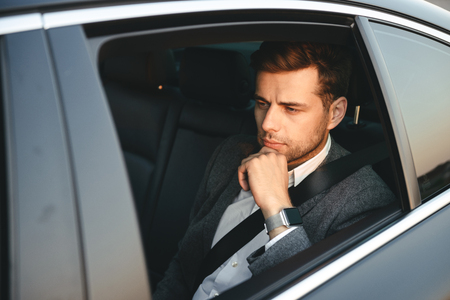 Portrait of serious caucasian man wearing businesslike suit back sitting while riding in car with safety belt