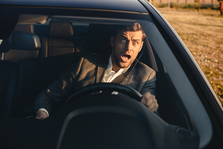 Portrait of a screaming businessman nearly crashing car during his trip, holding mobile phone